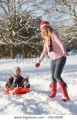 Mother Pulling Son On Sledge Through Snowy Landscape