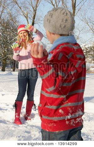 Mother And Son Having Snowball Fight In Snowy Landscape
