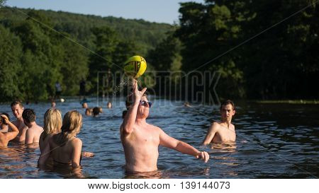 BATH UK - JULY 19 2016 Man throwing ball in River Avon, with swimmers. Hundreds flock to Warleigh Weir 3 miles from Bath on the hottest day of the year.