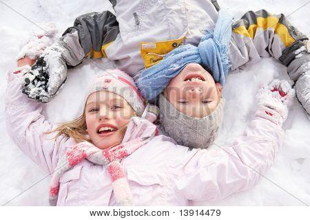 Children Laying On Ground Making Snow Angel