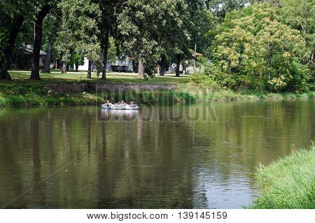 SHOREWOOD, ILLINOIS / UNITED STATES - AUGUST 30, 2015: People ride a raft down the Du Page River in Shorewood.