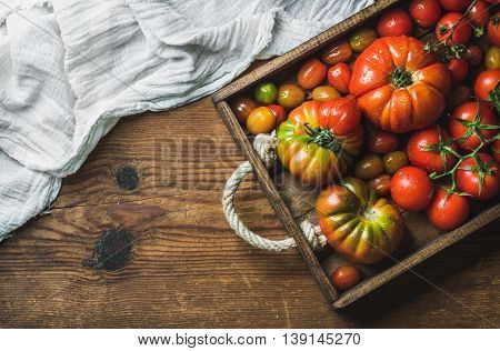 Colorful tomatoes of different sizes and kinds in dark wooden tray over rustic background, top view, copy space, horizontal composition