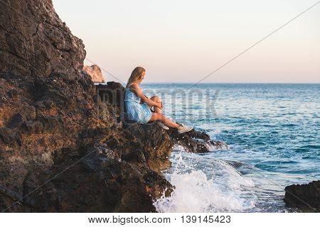 Young blond woman tourist in blue dress relaxing on stone rocks by the wavy sea at sunset and looking at water. Kleopatra beach, Alanya, Mediterranean region, Turkey