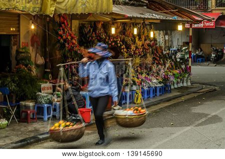 A Vietnamese woman carries baskets of fruit past flowers for sale on the streets of Hanoi