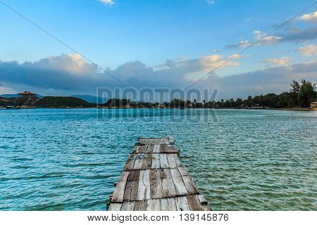 A wooden pier on turquoise water in a bay in Vietnam in the blue morning