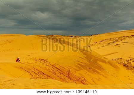 A Vietnamese woman sits on sand dunes under a stormy sky