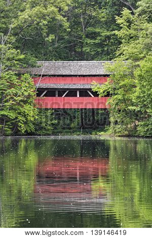 George Hutchins Covered Bridge is reflected on a pond in Alley Park south of Lancaster in Fairfield County Ohio.