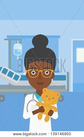 An african-american female pediatrician doctor holding a teddy bear on the background of hospital room. Vector flat design illustration. Vertical layout.
