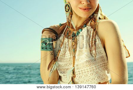 Female neck and hand with boho bracelets and necklace near sea, fashion portrait, white lace tank top, sunny backlit