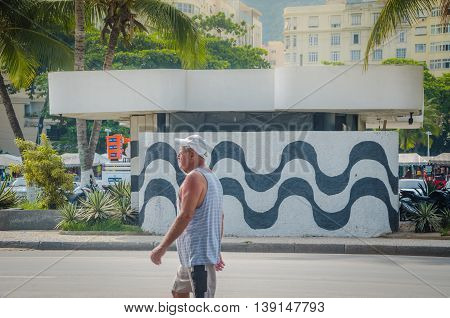 Man Walking Into Wall With Sidewalk Mosaic Of Copacabana Beach, Rio De Janeiro, Brazil.