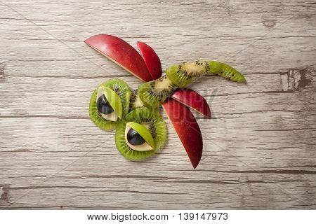Funny dragonfly made of fruits on isolated background
