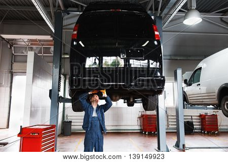 Minibus service maintenance, professional garage interior, lifted car on elevator