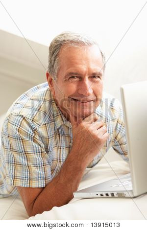 Senior Man Using Laptop Relaxing Sitting On Sofa At Home