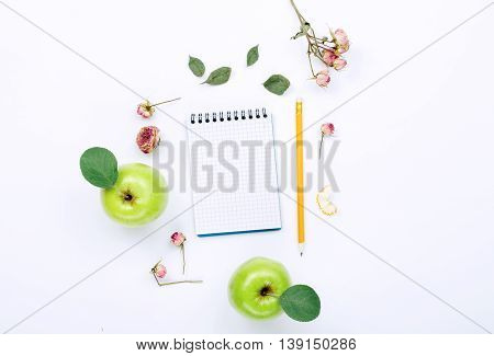 sketchbook with pencil green apples with leaves and dry rose flowers. Flat lay top view