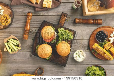Different burgers with grilled corn and snacks on the wooden table top view