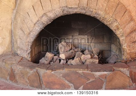 Arched reddish brown stone fireplace with piled wood inside hearth