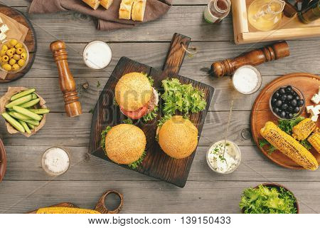 Different burgers with beer snacks and grilled corn on the wooden table top view
