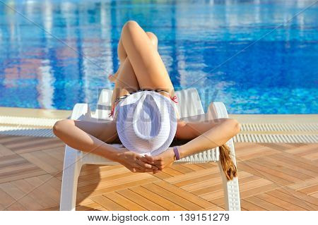 Woman In White Hat Lying On A Lounger Near The Swimming Pool. Sunbathing Woman
