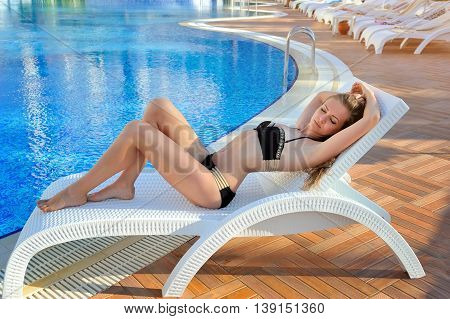 Sexy Young Woman Lying On A Lounger Near Swimming Pool With Blue Water