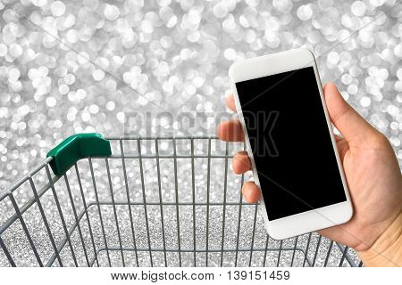 Woman hand holding smartphone against blur bokeh with shopping cart background