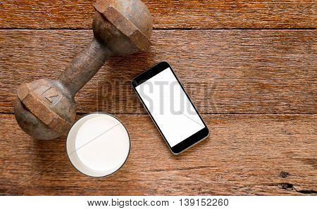 Smart phone and Iron dumbbell with milk on wooden floor.Top view focus.