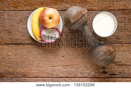 Iron dumbbell and milk with fruit (bananaappkedragon fruit) on wooden floor.Top view focus.