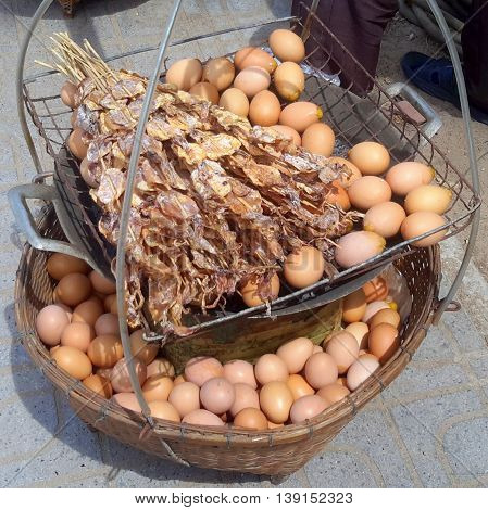 roasted/scrambled eggs in the shell heating over coals, dried squid on bamboo skewers for sale, all in wicker basket, usually carried hanging from a vendor's pole, Songkhla, Thailand
