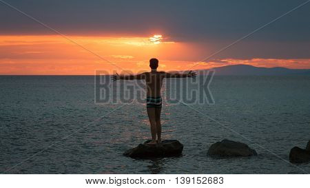 Young adult raising arms to the sea at sunset