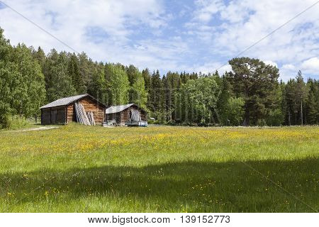 Wooden barn, timber building and wildflowers. Meadows this side.