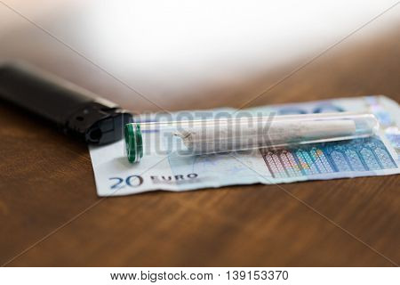 substance abuse, addiction, drug sale and smoking concept - close up of marijuana joint tube, money and lighter on table