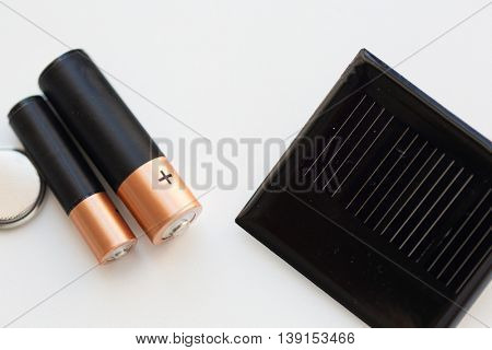 recycling, energy, power, environment and ecology concept - close up of alkaline batteries and solar cell