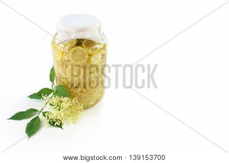 Sambucus nigra elderberry sirup with flower and leaves on white background. Pieces of elderberry with pieces of lemon in a glass of water.