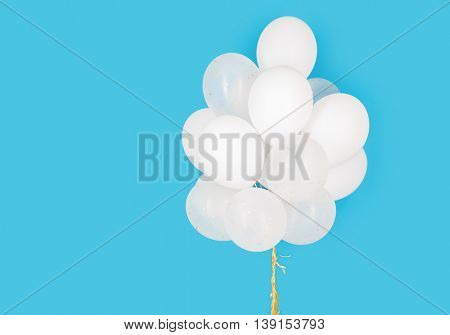 holidays, birthday, party and decoration concept - close up of inflated white helium balloons over blue background