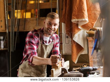 profession, people, carpentry, woodwork and people concept - happy carpenter with jointer planing wood plank at workshop