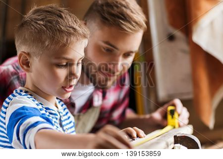 family, carpentry, woodwork and people concept - father and little son with ruler measuring wood plank at workshop
