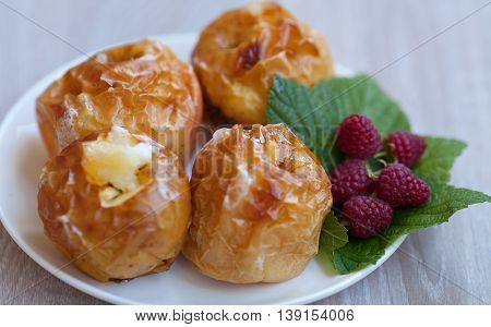 baked apples on white plate on wooden table.