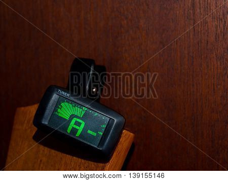 Clip tuner for Guitar A sound, wood background