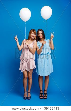 Portrait of two young beautiful girls in dresses looking at camera, holding baloons, smiling, resting at party over blue background.