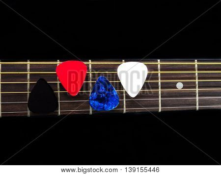 Three pick guitar on finger board background