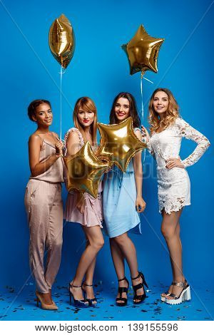 Four young beautiful girls in dresses looking at camera, smiling, laughing, holding baloons resting at party over blue background.