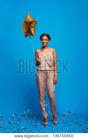 Portrait of young beautiful african girl looking at camera, holding baloon, smiling, resting at party over blue background.