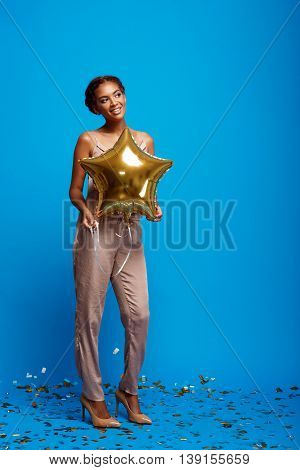 Portrait of young beautiful african girl holding baloon, smiling, resting at party over blue background. Copy space.