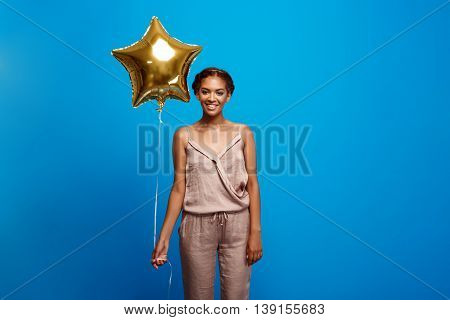 Portrait of young beautiful african girl looking at camera, holding baloon, smiling, resting at party over blue background. Copy space.