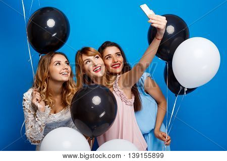 Three young beautiful girls in dresses making selfie, smiling, holding baloons at party over blue background.