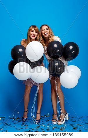 Portrait of two young beautiful girls in dresses looking at camera, holding baloons, laughing, resting at party over blue background.