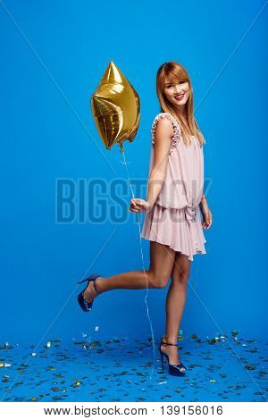 Portrait of young beautiful girl in dress holding baloon, looking at camera, smiling, resting at party over blue background.