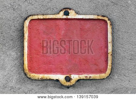 Close view of an old metallic red rusty plate on a stucco wall