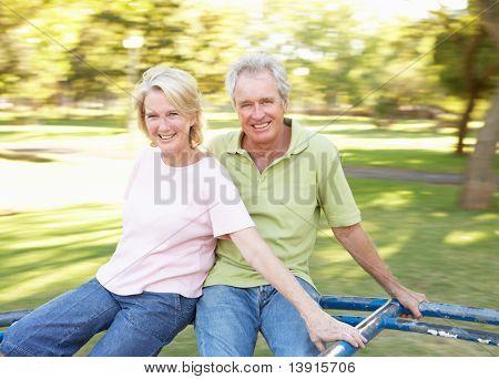 Senior Couple Reiten am Kreisverkehr in park