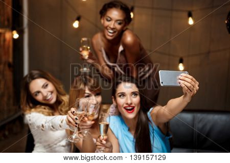 Four young beautiful girls in dresses making selfie, smiling, laughing  at party. Focus on phone.