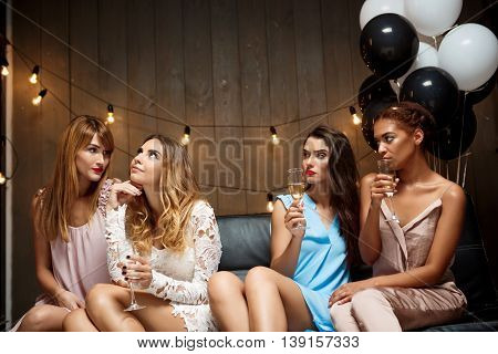 Four young beautiful girls in dresses gossiping, drinking champagne, resting at party.